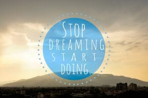 """text reading """"stop dreaming start doing"""" on a blue circle over a sunset"""